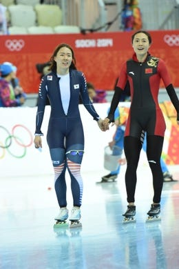Feb 11, 2014; Sochi, RUSSIA; Sang Hwa Lee (KOR) (left) is congratulated by Beixing Wang (CHN) after Lee won the gold medal after winning the gold medal in the ladies speed skating 500m at Adler Arena Skating Center during Sochi 2014 Olympic Winter Games. Mandatory Credit: Robert Hanashiro-USA TODAY Sports