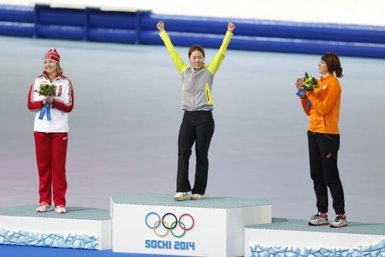 Feb 11, 2014; Sochi, RUSSIA; Sang Hwa Lee (KOR) (center) celebrates winning the gold medal in the ladies speed skating 500m at Adler Arena Skating Center during the Sochi 2014 Olympic Winter Games. Also pictured is bronze medal winner Margot Boer (NED) (right) and silver medal winner Olga Fatkulina (RUS). Mandatory Credit: Jeff Swinger-USA TODAY Sports