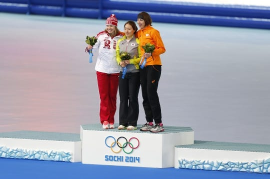 Feb 11, 2014; Sochi, RUSSIA; Sang Hwa Lee (KOR) (center), Olga Fatkulina (RUS) (left) , and Margot Boer (NED) (right) celebrate winning the gold, silver and bronze medals, respectively, in the ladies speed skating 500m at Adler Arena Skating Center during the Sochi 2014 Olympic Winter Games. Mandatory Credit: Jeff Swinger-USA TODAY Sports
