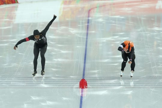 Feb 12, 2014; Sochi, RUSSIA; Shani Davis (USA) (left) and Koen Verweij (NED) cross the finish line during the mens speed skating 1000m at Adler Arena Skating Center during the Sochi 2014 Olympic Winter Games. Mandatory Credit: Winslow Townson-USA TODAY Sports