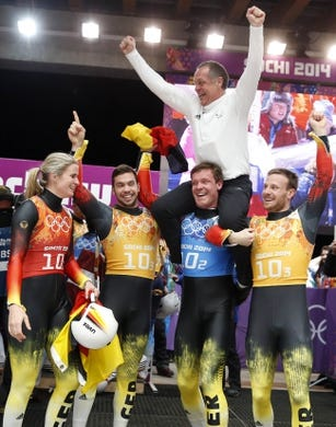 Feb 13, 2014; Krasnaya Polyana, RUSSIA; (From left to right) Germany luge athletes Natalie Geisenberger, Tobias Wendl, Felix Loch and Tobias Arlt celebrate with German national luge head coach Norbert Loch (top) after winning gold in the luge team relay during the Sochi 2014 Olympic Winter Games at Sanki Sliding Center. Mandatory Credit: Kevin Jairaj-USA TODAY Sports