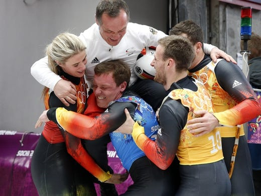 Feb 13, 2014; Krasnaya Polyana, RUSSIA; (From left to right) Germany luge athletes Natalie Geisenberger, Felix Loch, Tobias Arlt and Tobias Wendl celebrate with German national luge head coach Norbert Loch (top) after winning gold in the luge team relay during the Sochi 2014 Olympic Winter Games at Sanki Sliding Center. Mandatory Credit: Kevin Jairaj-USA TODAY Sports