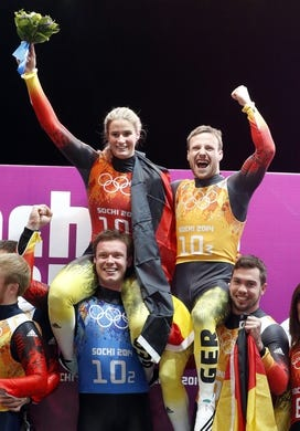 Feb 13, 2014; Krasnaya Polyana, RUSSIA; Natalie Geisenberger (top left), Felix Loch (bottom left), Tobias Wendl (bottom right), and Tobias Arlt (top right) celebrate with after winning gold in the luge team relay during the Sochi 2014 Olympic Winter Games at Sanki Sliding Center. Mandatory Credit: Kevin Jairaj-USA TODAY Sports