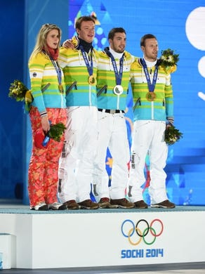 Feb 14, 2014; Sochi, RUSSIA; (Left to right) Natalie Geisenberger, Felix Loch, Tobias Wendl, Tobias Arlt of Germany sing their national anthem after receiving their gold medals during the medal ceremony for Luge Team Relay at the Sochi 2014 Olympic Winter Games at the Medals Plaza. Mandatory Credit: Kyle Terada-USA TODAY Sports