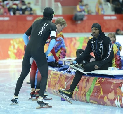 Feb 15, 2014; Sochi, RUSSIA;  Shani Davis, seated and a teammate in their speed suits after speed skating men's 1500m during the Sochi 2014 Olympic Winter Games at Adler Arena Skating Center. Mandatory Credit: Robert Hanashiro-USA TODAY Sports