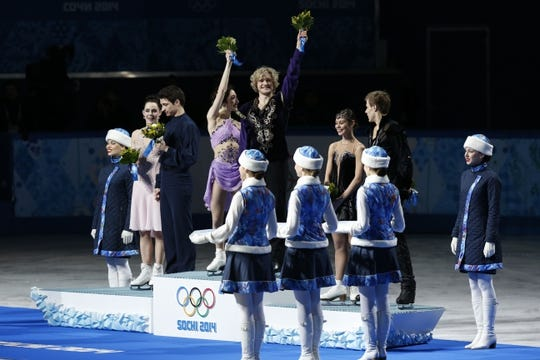 Feb 17, 2014; Sochi, RUSSIA; Charlie White and Meryl Davis (USA) (center) celebrate winning the gold medal in ice dance free dance program during the Sochi 2014 Olympic Winter Games at Iceberg Skating Palace. Also pictured is Scott Moir and Tessa Virtue (CAN) (left), and Nikita Katsalapov and Elena Ilinykh (RUS) (right). Mandatory Credit: Jeff Swinger-USA TODAY Sports