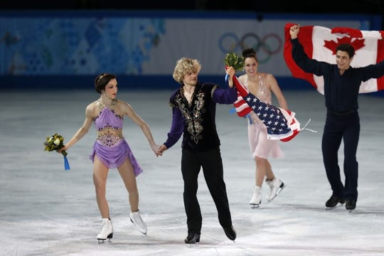 Feb 17, 2014; Sochi, RUSSIA; Charlie White and Meryl Davis (USA) (left) celebrate winning the gold medal in ice dance free dance program during the Sochi 2014 Olympic Winter Games at Iceberg Skating Palace. Also pictured is Scott Moir and Tessa Virtue (CAN). Mandatory Credit: Jeff Swinger-USA TODAY Sports