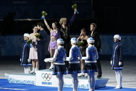 Feb 17, 2014; Sochi, RUSSIA; Charlie White and Meryl Davis (USA) (center) celebrate winning the gold medal in ice dance free dance program during the Sochi 2014 Olympic Winter Games at Iceberg Skating Palace. Also pictured is Scott Moir and Tessa Virtue (CAN) (left), and Nikita Katsalapov and Elena Ilinykh (RUS) (right), who won the silver and bronze medals, respectively. Mandatory Credit: Jeff Swinger-USA TODAY Sports