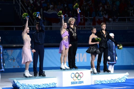 Feb 17, 2014; Sochi, RUSSIA; Charlie White and Meryl Davis (USA) (center) and Scott Moir and Tessa Virtue (CAN) (left) celebrate winning the gold and silver medals, respectively, in the ice dance free dance program during the Sochi 2014 Olympic Winter Games at Iceberg Skating Palace. Also pictured is Nikita Katsalapov and Elena Ilinykh (RUS) (right), who won the bronze medal. Mandatory Credit: Robert Deutsch-USA TODAY Sports