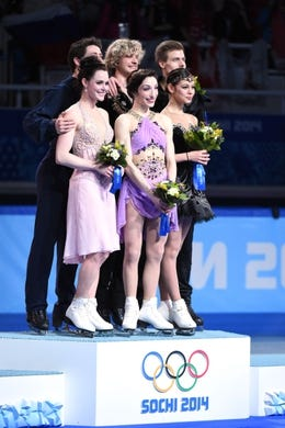 Feb 17, 2014; Sochi, RUSSIA; Charlie White and Meryl Davis (USA) (center), Scott Moir and Tessa Virtue (CAN) (left), and Nikita Katsalapov and Elena Ilinykh (RUS) (right) celebrate winning the gold, silver, and bronze medals, respectively, in the ice dance free dance program during the Sochi 2014 Olympic Winter Games at Iceberg Skating Palace. Mandatory Credit: Robert Deutsch-USA TODAY Sports