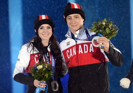 Feb 18, 2014; Sochi, RUSSIA; Tessa Virtue (left) and Scott Moir (right), of Canada, pose after receiving their silver medals during the medal ceremony for Figure Skating Ice Dance during the Sochi 2014 Olympic Winter Games at the Medals Plaza. Mandatory Credit: Jayne Kamin-Oncea-USA TODAY Sports
