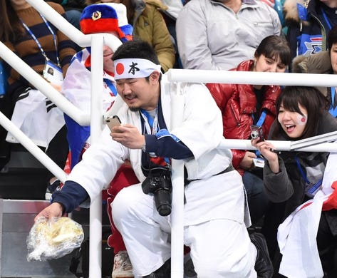 Feb 20, 2014; Sochi, RUSSIA; Japanese fans of Mao Asada hand down items after her performance in the ladies free skate program during the Sochi 2014 Olympic Winter Games at Iceberg Skating Palace. Mandatory Credit: Robert Deutsch-USA TODAY Sports