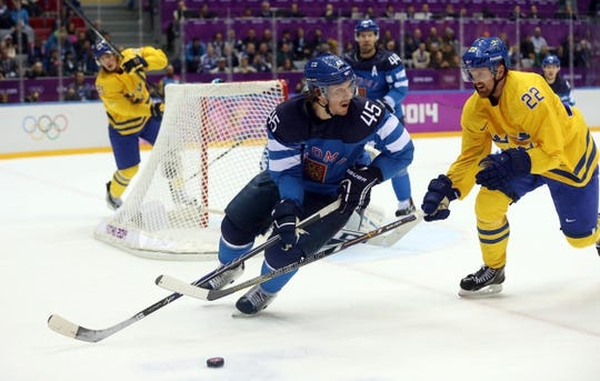 Feb 21, 2014; Sochi, RUSSIA; Finland defenseman Sami Vatanen (45) skates with the puck past Sweden forward Daniel Sedin (22) in the men's ice hockey semifinals during the Sochi 2014 Olympic Winter Games at Bolshoy Ice Dome. Mandatory Credit: Winslow Townson-USA TODAY Sports