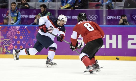 Feb 21, 2014; Sochi, RUSSIA; USA forward Zach Parise (9) shoots the puck past Canada defenseman Drew Doughty (8) in the men's ice hockey semifinals during the Sochi 2014 Olympic Winter Games at Bolshoy Ice Dome. Mandatory Credit: Scott Rovak-USA TODAY Sports