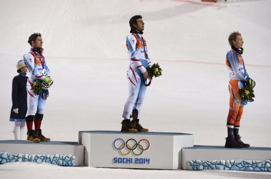 Feb 22, 2014; Krasnaya Polyana, RUSSIA; Mario Matt (AUT, center), Marcel Hirscher (AUT, left) and Henrik Kristoffersen (NOR, right) stands at attention while listening to the national anthem of Austria after men's alpine skiing slalom during the Sochi 2014 Olympic Winter Games at Rosa Khutor Alpine Center. Mandatory Credit: Jack Gruber-USA TODAY Sports