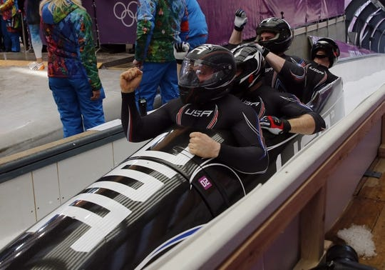 Feb 23, 2014; Krasnaya Polyana, RUSSIA; (From left to right) USA-1 piloted by Steven Holcomb with Curtis Tomasevicz, and Steven Langton, and Christopher Fogt react after heat four of men's four-man bobsleigh during the Sochi 2014 Olympic Winter Games at Sanki Sliding Center. USA-1 won bronze. Mandatory Credit: Kevin Jairaj-USA TODAY Sports
