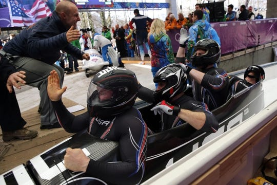 Feb 23, 2014; Krasnaya Polyana, RUSSIA; (From left to right) USA-2 pilot Nick Cunningham high-fives USA-1 teammates Steven Holcomb with Curtis Tomasevicz, and Steven Langton, and Christopher Fogt react after heat four of men's four-man bobsleigh during the Sochi 2014 Olympic Winter Games at Sanki Sliding Center. USA-1 won bronze. Mandatory Credit: Kevin Jairaj-USA TODAY Sports