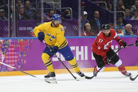 Feb 23, 2014; Sochi, RUSSIA; Sweden forward Daniel Sedin (22) and Canada forward Patrice Bergeron (37) battle for the puck in the men's ice hockey gold medal game during the Sochi 2014 Olympic Winter Games at Bolshoy Ice Dome. Mandatory Credit: Winslow Townson-USA TODAY Sports
