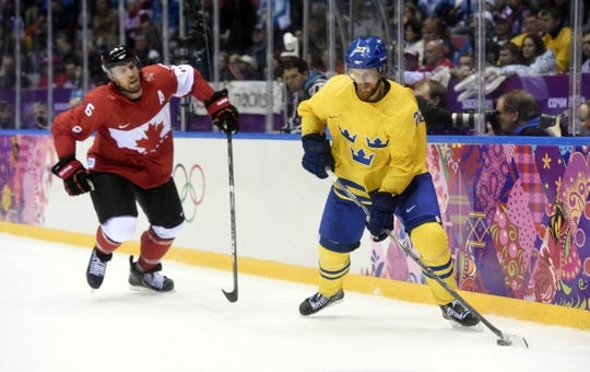 Feb 23, 2014; Sochi, RUSSIA; Sweden forward Daniel Sedin (22) controls the puck against Canada defenseman Shea Weber (6) in the men's ice hockey gold medal game during the Sochi 2014 Olympic Winter Games at Bolshoy Ice Dome. Mandatory Credit: Eric Bolte-USA TODAY Sports