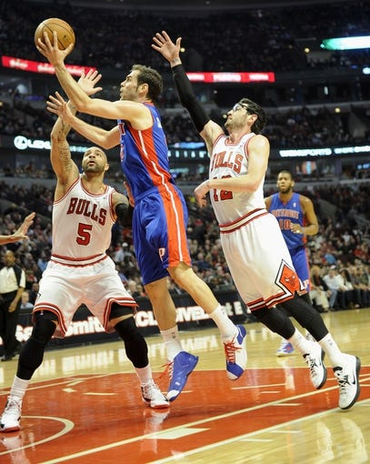 Mar 31, 2013; Chicago, IL, USA;  Detroit Pistons point guard Jose Calderon (8) shoots as he is defended by Chicago Bulls power forward Carlos Boozer (5) and shooting guard Kirk Hinrich (12) during the first half at the United Center. Mandatory Credit: David Banks-USA TODAY Sports