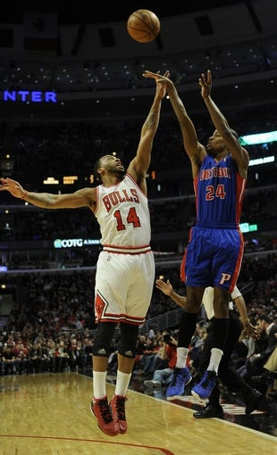 Mar 31, 2013; Chicago, IL, USA; Detroit Pistons shooting guard Kim English (24) shoots over Chicago Bulls shooting guard Daequan Cook (14) during the first half at the United Center. Mandatory Credit: David Banks-USA TODAY Sports