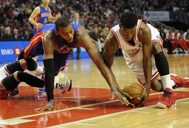 Mar 31, 2013; Chicago, IL, USA; Detroit Pistons center Greg Monroe (left) and Chicago Bulls small forward Jimmy Butler (21) reach for a loose ball during the first half at the United Center. Mandatory Credit: David Banks-USA TODAY Sports