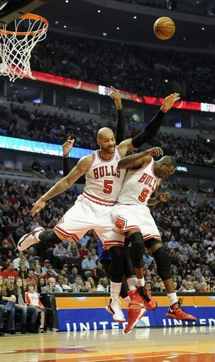 Mar 31, 2013; Chicago, IL, USA; Chicago Bulls power forward Carlos Boozer (5) and small forward Luol Deng (9) reach for a rebound during the first half against the Detroit Pistons at the United Center. Mandatory Credit: David Banks-USA TODAY Sports