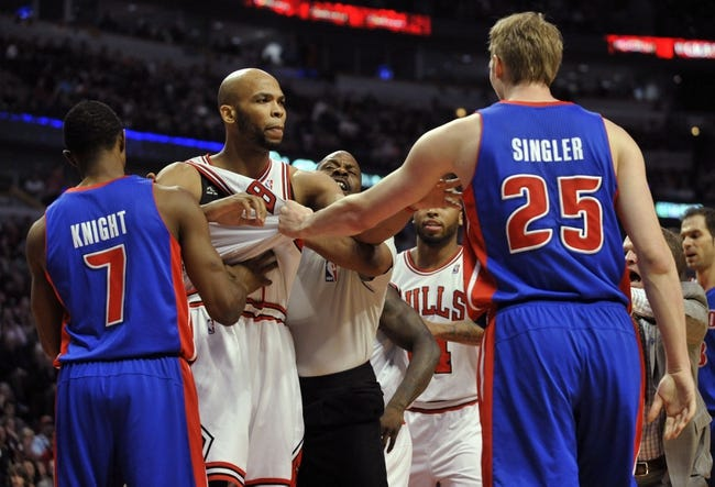 Mar 31, 2013; Chicago, IL, USA; Detroit Pistons point guard Brandon Knight (7) and Detroit Pistons point guard Brandon Knight (7) get into a shoving match with Chicago Bulls power forward Taj Gibson (22) during the first half at the United Center. Mandatory Credit: David Banks-USA TODAY Sports