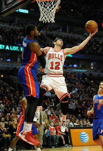 Mar 31, 2013; Chicago, IL, USA; Chicago Bulls shooting guard Kirk Hinrich (12) is defended by Detroit Pistons center Andre Drummond (1) during the second half at the United Center. The Chicago Bulls defeated the Detroit Pistons 95-94. Mandatory Credit: David Banks-USA TODAY Sports