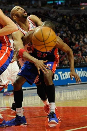 Mar 31, 2013; Chicago, IL, USA;  Chicago Bulls power forward Taj Gibson (22) and Detroit Pistons shooting guard Kim English (24) get tangled up going for the ball during the second half at the United Center. The Chicago Bulls defeated the Detroit Pistons 95-94. Mandatory Credit: David Banks-USA TODAY Sports