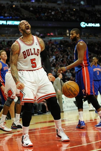 Mar 31, 2013; Chicago, IL, USA; Chicago Bulls power forward Carlos Boozer (5) reacts after dunking over Detroit Pistons center Greg Monroe (10) during the second half at the United Center. The Chicago Bulls defeated the Detroit Pistons 95-94. Mandatory Credit: David Banks-USA TODAY Sports