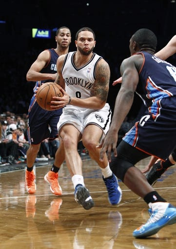 Apr 6, 2013; Brooklyn, NY, USA; Brooklyn Nets guard Deron Williams (8) drives to the basket against Charlotte Bobcats guard Jannero Pargo (5) and guard Ben Gordon (8) at Barclays Center. Nets won 105-96. Mandatory Credit: Nicole Sweet-USA TODAY Sports