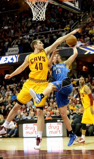 Apr 7, 2013; Cleveland, OH, USA; Orlando Magic point guard Beno Udrih (19) is fouled by Cleveland Cavaliers center Tyler Zeller (40) while going up for a shot during the game at Quicken Loans Arena. Mandatory Credit: Eric P. Mull-USA TODAY Sports