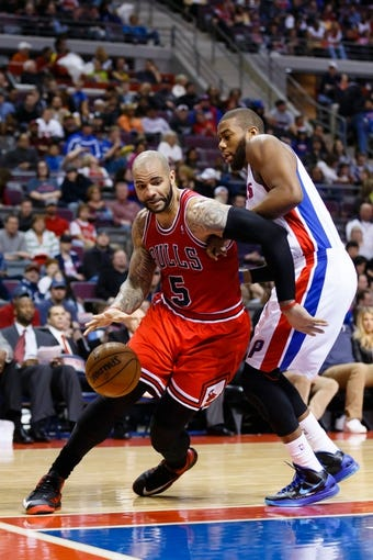 April 7, 2013; Auburn Hills, MI, USA; Chicago Bulls power forward Carlos Boozer (5) moves the ball on Detroit Pistons center Greg Monroe (10) in the second quarter at The Palace. Mandatory Credit: Rick Osentoski-USA TODAY Sports