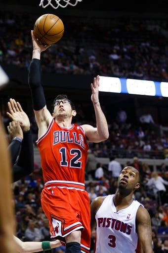 April 7, 2013; Auburn Hills, MI, USA; Chicago Bulls shooting guard Kirk Hinrich (12) goes to the basket against Detroit Pistons point guard Rodney Stuckey (3) in the second quarter at The Palace. Mandatory Credit: Rick Osentoski-USA TODAY Sports