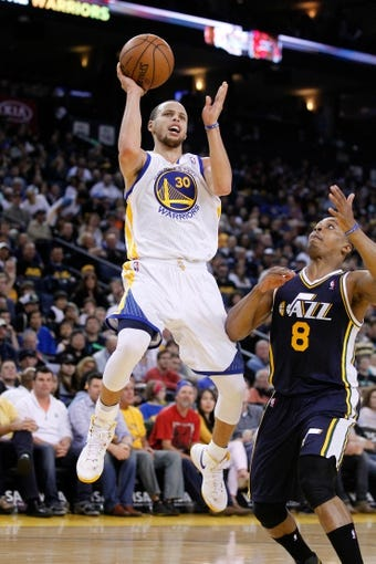 Apr 7, 2013; Oakland, CA, USA; Golden State Warriors guard Stephen Curry (30) attempts a shot over Utah Jazz guard Randy Foye (8) in the second quarter at ORACLE arena. Mandatory Credit: Cary Edmondson-USA TODAY Sports