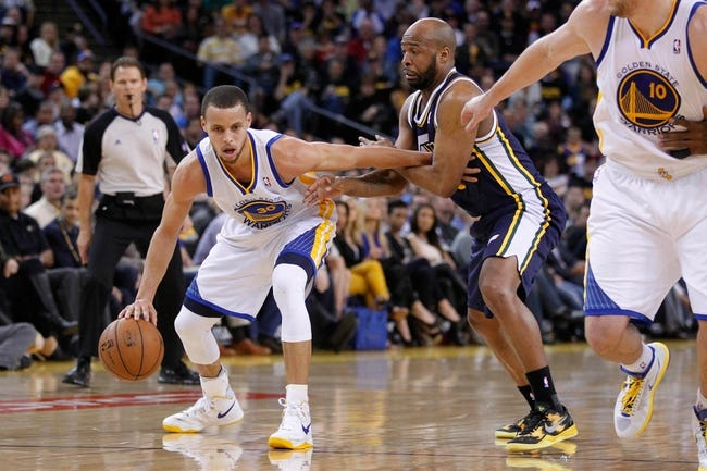 Apr 7, 2013; Oakland, CA, USA; Golden State Warriors guard Stephen Curry (30) keeps the ball away from the reach of Utah Jazz guard Jamaal Tinsley (6) in the second quarter at ORACLE arena. Mandatory Credit: Cary Edmondson-USA TODAY Sports
