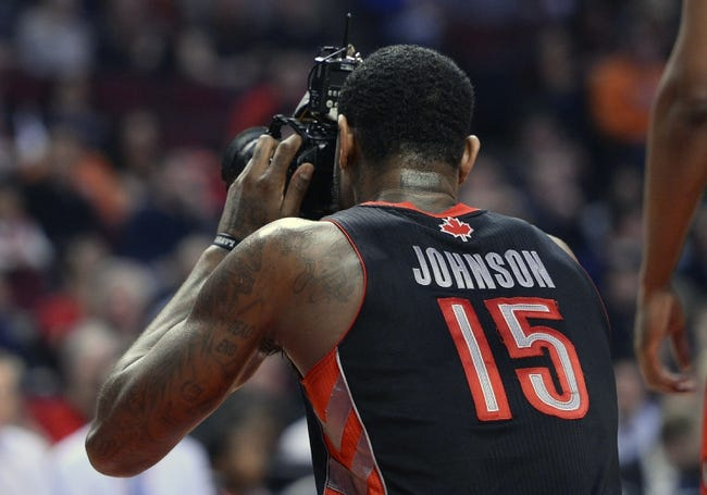 Apr 9, 2013; Chicago, IL, USA; Toronto Raptors power forward Amir Johnson (15) takes a picture of his teammates after a camera was kicked onto the game floor during play against the Chicago Bulls during the first half at the United Center. Mandatory Credit: Mike DiNovo-USA TODAY Sports