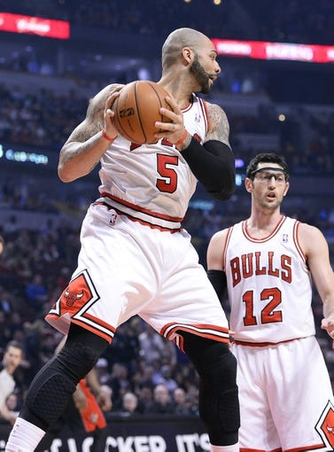 Apr 9, 2013; Chicago, IL, USA; Chicago Bulls power forward Carlos Boozer (5) grabs a rebound against the Toronto Raptors during the first half at the United Center. Mandatory Credit: Mike DiNovo-USA TODAY Sports