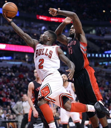 Apr 9, 2013; Chicago, IL, USA; Chicago Bulls point guard Nate Robinson (2) shoots the ball against Toronto Raptors power forward Amir Johnson (15) during the second half at the United Center. Toronto defeats Chicago 101-98. Mandatory Credit: Mike DiNovo-USA TODAY Sports