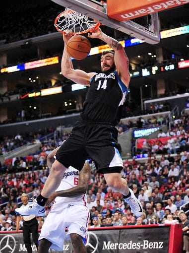 April 10, 2013; Los Angeles, CA, USA; Minnesota Timberwolves center Nikola Pekovic (14) dunks to score a basket against the Los Angeles Clippers during the first half at Staples Center. Mandatory Credit: Gary A. Vasquez-USA TODAY Sports