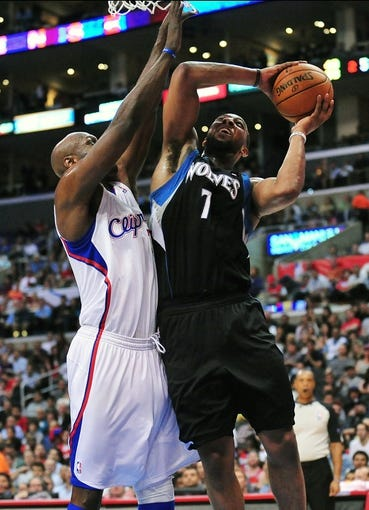 April 10, 2013; Los Angeles, CA, USA; Minnesota Timberwolves power forward Derrick Williams (7) moves to the basket against the defense of Los Angeles Clippers power forward Lamar Odom (7) during the first half at Staples Center. Mandatory Credit: Gary A. Vasquez-USA TODAY Sports