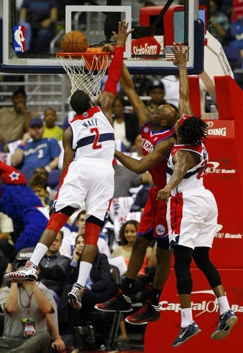 Apr 12, 2013; Washington, DC, USA; Philadelphia 76ers power forward Arnett Moultrie (5) attempts to dunk the ball as Washington Wizards point guard John Wall (2) and Wizards power forward Cartier Martin (20) defend in the first quarter at Verizon Center. Mandatory Credit: Geoff Burke-USA TODAY Sports