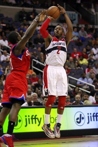 Apr 12, 2013; Washington, DC, USA; Washington Wizards point guard John Wall (2) shoots the ball as Philadelphia 76ers point guard Jrue Holiday (11) defends in the second quarter at Verizon Center. Mandatory Credit: Geoff Burke-USA TODAY Sports