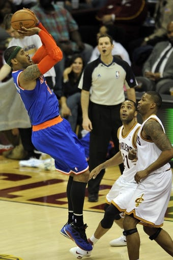Apr 12, 2013; Cleveland, OH, USA; New York Knicks small forward Carmelo Anthony (7) makes a basket over Cleveland Cavaliers shooting guard Wayne Ellington (21) and small forward Alonzo Gee (33) in the second quarter at Quicken Loans Arena. Mandatory Credit: David Richard-USA TODAY Sports
