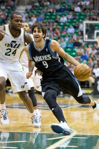 Apr 12, 2013; Salt Lake City, UT, USA; Minnesota Timberwolves point guard Ricky Rubio (9) dribbles around Utah Jazz power forward Paul Millsap (24) during the first quarter at EnergySolutions Arena. Mandatory Credit: Russ Isabella-USA TODAY Sports
