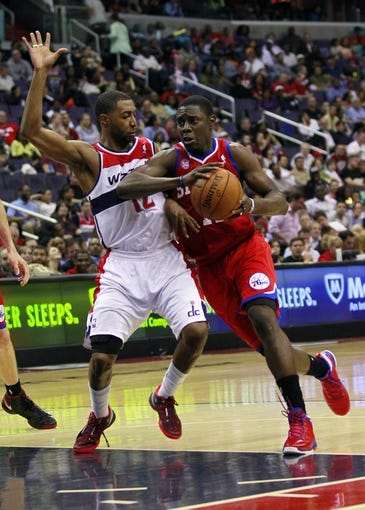 Apr 12, 2013; Washington, DC, USA; Philadelphia 76ers point guard Jrue Holiday (11) dribbles the ball as Washington Wizards point guard A.J. Price (12) defends in the fourth quarter at Verizon Center. The 76ers won 97-86. Mandatory Credit: Geoff Burke-USA TODAY Sports