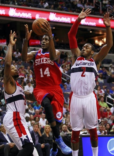Apr 12, 2013; Washington, DC, USA; Philadelphia 76ers shooting guard Justin Holiday (14) shoots the ball as Washington Wizards power forward Cartier Martin (20) and Wizards point guard John Wall (2) defend in the fourth quarter at Verizon Center. The 76ers won 97-86. Mandatory Credit: Geoff Burke-USA TODAY Sports