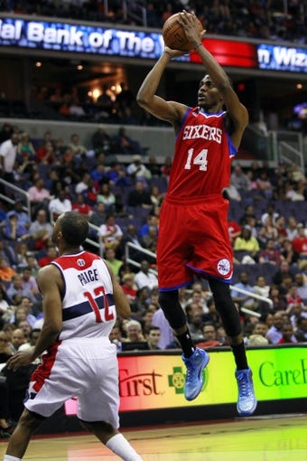 Apr 12, 2013; Washington, DC, USA; Philadelphia 76ers shooting guard Justin Holiday (14) shoots the ball over Washington Wizards point guard A.J. Price (12) in the fourth quarter at Verizon Center. The 76ers won 97-86. Mandatory Credit: Geoff Burke-USA TODAY Sports