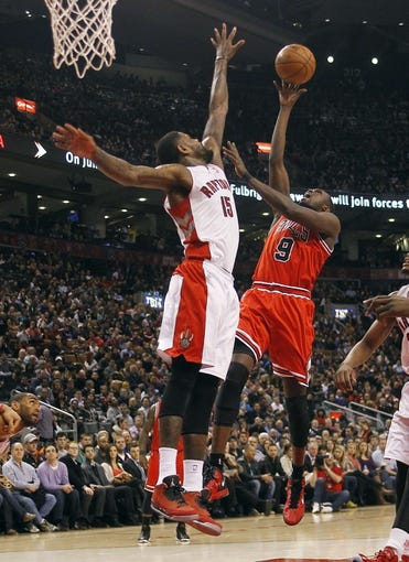 Apr 12, 2013; Toronto, Ontario, CAN; Toronto Raptors center-forward Amir Johnson (15) defends against Chicago Bulls forward Luol Deng (9) during the first half at the Air Canada Centre. Toronto defeated Chicago 97-88. Mandatory Credit: John E. Sokolowski-USA TODAY Sports